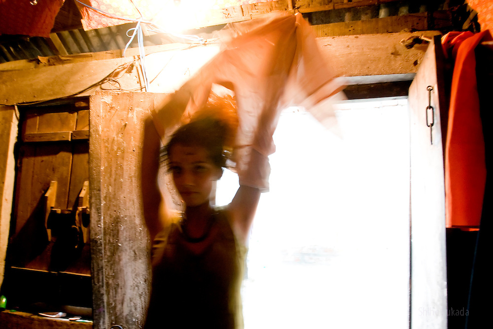 Sex worker Shetu, 17, changes her clothes at brothel in Tangail, Bangladesh.