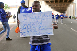 """JOHANNESBURG, SOUTH AFRICA – APRIL 07: A man  kneels with a placard reading """"Gwede, Ciryl Ramaphosa, don't be afraid of Zuma"""" as DA (Democratic Alliance) supporters march in protest as part of a nationwide call for President Zuma to step down, in Johannesburg, South Africa, 07 April 2017. Businesses closed and South Africans from numerous political, religious, labour and civic groups gathered at central points across the entire country protesting against President Zuma's recent government reshuffle appointing 10 new ministers and 10 new deputy ministers including the axing of the finance minister. Photo: Dino Lloyd"""