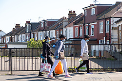 © Licensed to London News Pictures. 22/04/2020. London, UK. People wearing a face masks walk down Ealing Road, Alperton. The start of the Muslim observation of Ramadan will begin during the Coronavirus lockdown.  Photo credit: Ray Tang/LNP