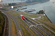 Nederland, Zuid-Holland, Rotterdam, 19-09-2009; Rozenburg, A15  met ingang Burgemeester Thomassentunnel onder het Caland Kanaal, in de achtergrond het betonnen windscherm op de oever van het Calandkanaal ten behoeve van hoge containerschepen.Rozenburg, motorway A15 with Burgemeester  Thomassen Tunnel under Caland Canal, in the background, the concrete windshield on the banks of the Caland Canal for high container ships.luchtfoto (toeslag), aerial photo (additional fee required).foto/photo Siebe Swart