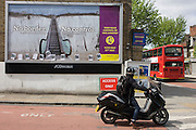 Passing motorcyclist looks at the anti-EU 'UK Independence Party's (UKIP) political billboard shows an escalator leading up the white cliffs of Dover (a metaphor for unrestricted immigration access to Britain) in East Dulwich - a relatively affluent district of south London. The ad is displayed before European elections on 22nd May and UKIP's controversial right-wing policy of no foreigners into the UK to take British jobs, is promising to do well in the forthcoming election.