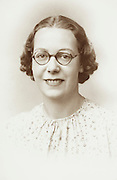 vintage formal studio portrait of an adult female person wearing glasses