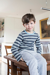 Portrait of boy sitting on table, smiling