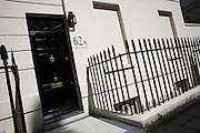 Immaculate railings and heavy gloss-painted doorway of flat number 62a in exclusive Eaton Square, Belgravia.