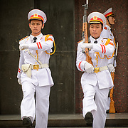 Two soldiers goosestep their way to the entrance of the Ho Chi Minh Mausoleum as part of the changing of the guard ceremony, while one of the new guards is seen at attention in the background.  A large memorial in downtown Hanoi surrounded by Ba Dinh Square, the Ho Chi Minh Mausoleum houses the embalmed body of former Vietnamese leader and founding president Ho Chi Minh.