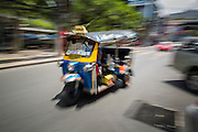 """15 JULY 2014 - BANGKOK, THAILAND: A """"tuk-tuk"""" or three wheeled taxi, in Siam Square, a shopping and entertainment area in Bangkok. There is a range of shops and services, including tutor schools, restaurants, cafe, designer clothing boutiques, record stores, bookshops, Hard Rock Cafe and banks in the area. Siam Square is owned by Chulalongkorn University and is managed by its Property Management Office, known as the Chula Property.    PHOTO BY JACK KURTZ"""