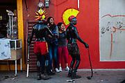 Dos Xinacates enmascarados y pintados con aceite vegetal y pigmento negro acorralan a tres mujeres para pedirles algunas monedas a cambio de no mancharles la ropa o la cara durante el carnaval de San Nicolás de los Ranchos.