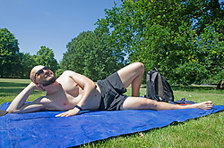© Licensed to London News Pictures 16/06/2021. Greenwich, UK. A young man sunbathing in Greenwich park, London enjoying the warm weather. Today could be the hottest day of the year so far with temperatures predicted to hit 30C. Photo credit:Grant Falvey/LNP