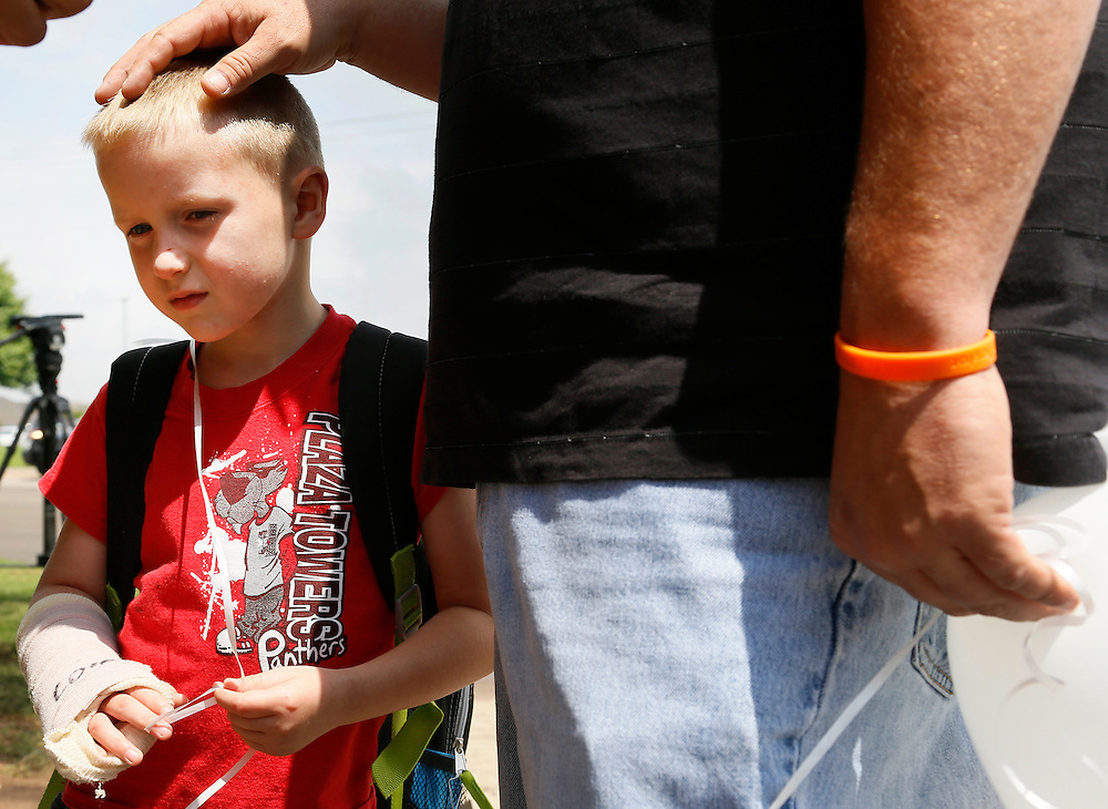 Kaden Shippers, 6, injured in the  Plaza Towers elementary school May 20, 3013 tornado and wearing a Plaza Towers shirt,  listens to his father talking to a reporter after being dismissed on the last day of school in Oklahoma City, May 23, 2013. Kaden has staples in his head, forty stitches in his back and hurt his arm in storm. Seven children died in the school with the first being laid to rest today. REUTERS/Rick Wilking (UNITED STATES)