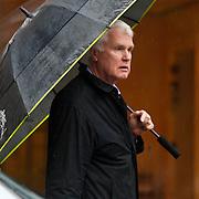 NLD/Amsterdam/20100807 - Adriaan van Dis lopend met een paraplu in de regen