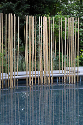 White stone path floating above pool with architectural use of bamboo sticks reflecting in the water.