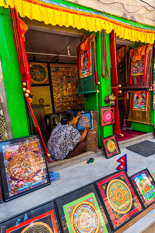 Artist painting a mandala, as other mandalas and thangkas hang in a shop in Patan (Lalitpur), Nepal.