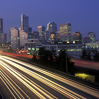 USA, Washington, Seattle, Traffic lights during morning rush hour on I-5 and downtown city skyline before sunrise