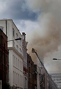 Firefighters tackle the fire. A fire broke out on Dean Streen in Soho, Central London on Friday afternoon. The fire, in a five storey building in the heart of the city raged with firefighters struggling to get the blaze under control. In the nearby streets workers finishing early stood in the smoke filled streets having an end-of-the-week beer in the ghostly atmosphere.