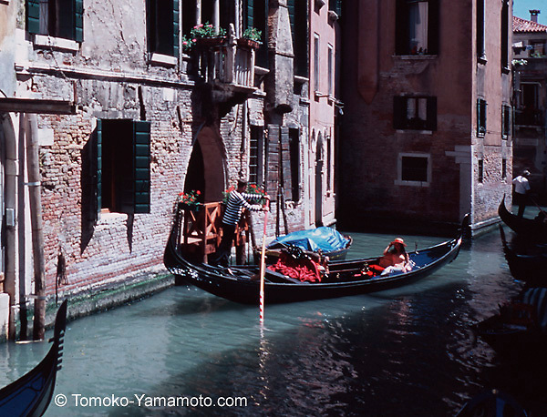 One gondola after another follows in a side canal in Venice, Italy.  The brick façade of the building near the central gondola looks old but a wood balcony facing the canal looks freshly painted.  A young woman with a hat on rides in the central gondola rowed by a gondolier in a striped shirt and the next gondola in line is seen by its ferro.  The centra gondola moves through the sunny spot in the center. The woman's hat has a red ribbon and she is wearing pink top and white pants. She is holding down the hat with both of her hands.  The ferro symbolizes six sestieri of Venice with six teeth and a Doge's cap is on top of the teeth. The house behind the central gondola has a Venetian Gothic façade. Window boxes with flowers and green shutters add colors to this photo.<br /> This photo has been cropped to emphasize the central gondola, but the original shows the entire Venetian Gothic façade of three windows above the flower boxes. Photo of Venice, Italy by Tomoko Yamamoto. Original on 35mm slide film. Foto der Gondelfahrt im Seitenkanal in Venedig, Italien.  Venezia, Italia.