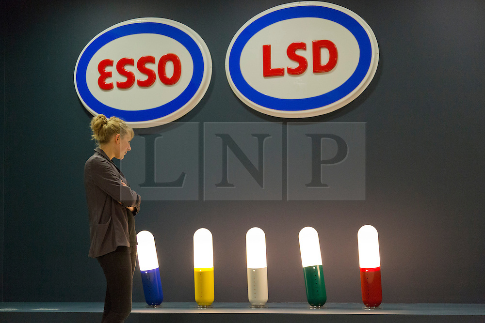 "© Licensed to London News Pictures. 21/10/2013. London, England. A museum worker stands in front of lights in pill-shapes and Esso/LSD designs. The Exhibition ""Pop Art Design"" opens at the Barbican Art Gallery/Barbican Centre running from 22 October 2013 to 9 February 2014. The exhibition brings together 200 works by 70 artists and designers including Peter Blake, Andy Warhol and Roy Lichtenstein. Photo credit: Bettina Strenske/LNP"