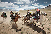 Kyrgyz men fight in a game of Buzkashi, a competition akin to polo?except a headless goat carcass takes the place of the ball. .Buzkachi is almost exclusively played during weddings..Probably one of the great pleasures in the life of a Kyrgyz man, Buzkashi is Afghanistan's national sport. The Kyrgyz call it ulak tartysh, or ?goat grabbing.?.At the wedding celebration