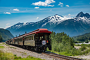 The White Pass and Yukon Route is a narrow-gauge railroad built in 1900 linking the port of Skagway, Alaska, with Whitehorse, the capital of Yukon in Canada. Recapturing the Gold Rush era, it is the most popular land excursion from Alaska cruises. Isolated from any other railroad system, its equipment, freight and passengers are ferried by ship via the Port of Skagway, and by road at a few stops. It was built 1898-1900 during the Klondike Gold Rush to reach the goldfields, and became the primary route to the interior of the Yukon, replacing the Chilkoot Trail and other routes. The route continued operation until 1982, and in 1988 was partially revived as a heritage railway. Skagway was founded in 1897 on the Alaska Panhandle. Half of Alaska's total visitors come via cruise ships. Klondike Gold Rush National Historical Park commemorates the late 1890s Gold Rush with three units in Municipality of Skagway Borough: Historic Skagway; the White Pass Trail; and Dyea Townsite and Chilkoot Trail. (A fourth unit is in Pioneer Square National Historic District in Seattle, Washington.)