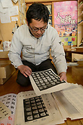 Masahara Nakajima, owner of Nakajima Seikichi Shoten, looking at calligraphy designs for shogi playing pieces. Tendo, Yamagata Prefecture, Japan, February 19, 2018. The city of Tendo in Yamagata Prefecture is famous for its shogi (Japanese chess) playing pieces. Production started early in the 19th century and Tendo still produces over 95% of the Shogi pieces made in Japan.