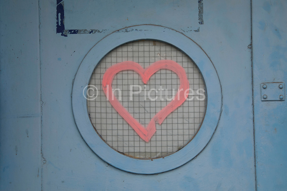 Love heart graffiti on a round window in Birmingham, United Kingdom.