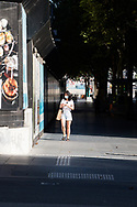 A woman walks down an empty Swanston Street on the first day of a five day snap lockdown in Victoria due to COVID-19 outbreak originating at The Holiday Inn. The entire state is returning to harsh stage-four lockdowns until Wednesday at 11.59pm as health authorities struggle to contain the Holiday Inn coronavirus outbreak.