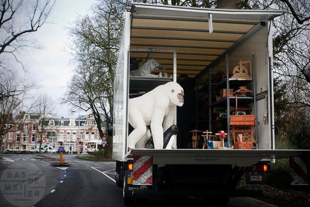 Een vrachtwagen met allerlei speelgoed, waaronder een grote nepgorilla, wordt gelost