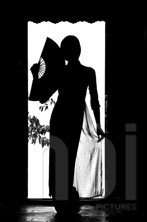 A Vietnamese woman silhouetted in a doorway wears a traditional Ao Dai and holds an open fan in her hand, Khanh Hoa province, Vietnam, Southeast Asia