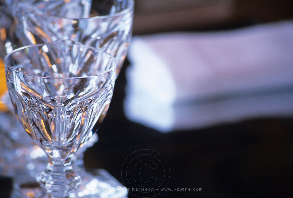 """The famous best selling Harcourt glass on a shining metal table with a linen serviette napkin at the Baccarat Restaurant """"Le Cristal Room"""", in the old dining room. Designed by Philippe Starck...The Cristal Room restaurant: One of Baccarat's bestsellers - the Harcourt glass"""