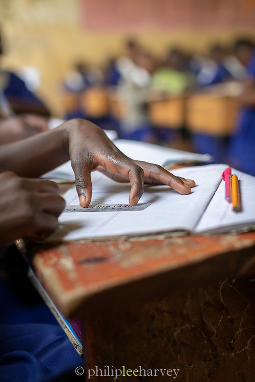 Close-up of school children drawing in textbook using ruler, The Musoto Christian School, Uganda