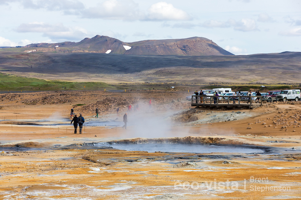 Sulphur enriched soil and colours surrounding one of the bubbling pools, with people walking in the background. The carpark and one of the viewing platforms are also visible in the background. Namafjall Geothermal Area, Myvatn, Iceland. July.