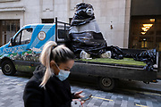 A woman walks past the second of two giant Christmas decoration bears which are being offloaded from a sub-contractor's lorry and delivered to the foyer of the Cafe Royal in Air Street, on 1st December 2020, in London, England. The bears have been manufactured by Romanian Eugeniu Dumneanu's Art-Grass company, a synthetic grass and turf provider specialising in the covering of surfaces and instillations with artificial grass and Astroturf.