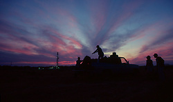 Stock photo of the silhouette of four men loading hay into a pickup truck with an oil and gas drilling rig in the background at sunset in Texas