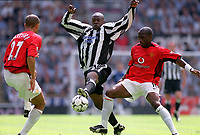 Shola Ameobi (Newcastle) between Eric Djemba-Djemba and Mikael Silvestre (Manchester United) Newcastle United v Manchester United, FA Premiership, 23/08/2003. Credit: Colorsport / Matthew Impey