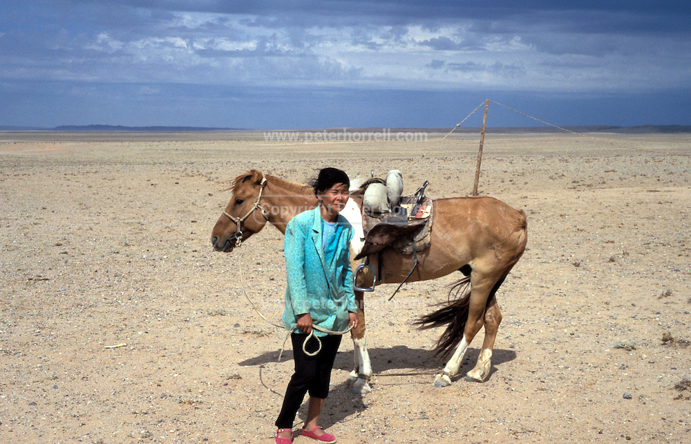 Mongolia, Gobi desert. July 1996: Munkhtsetseg's sister poses with her horse in the Gobi desert.
