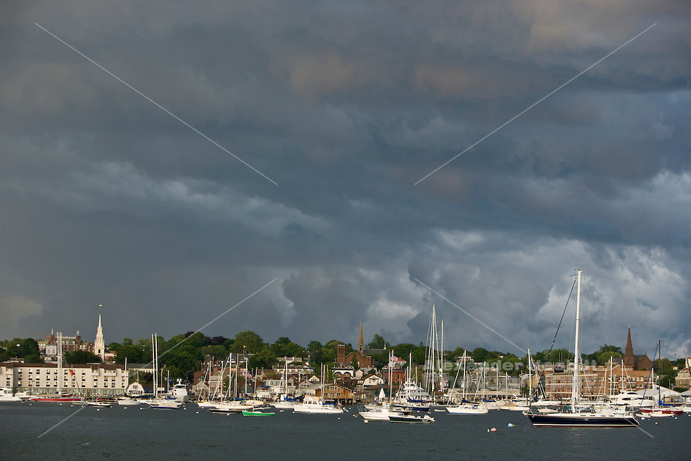 Newport, RI USA -  A passing thunderstorm with dramatic clouds passes over the boats in moored in the  harbor and the downtown.