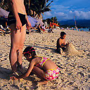 An asian family play in the sand at White Beach, Boracay Island, the Philippines on October 3, 2008, Photo Tim Clayton..Asian tourists at White Beach, Boracay Island, the Philippines...The 4 km stretch of White beach on Boracay Island, the Philippines has been honoured as the best leisure destination in Asia beating popular destinations such as Bali in Indonesia and Sanya in China in a recent survey conducted by an International Travel Magazine with 2.2 million viewers taking part in the online poll...Last year, close to 600,000 visitors visited Boracay with South Korea providing 128,909 visitors followed by Japan, 35,294, USA, 13,362 and China 12,720...A popular destination for South Korean divers and honeymooners, Boracay is now attracting crowds of tourists from mainland China who are arriving in ever increasing numbers. In Asia, China has already overtaken Japan to become the largest source of outland travelers...Boracay's main attraction is 4 km of pristine powder fine white sand and the crystal clear azure water making it a popular destination for Scuba diving with nearly 20 dive centers along White beach. The stretch of shady palm trees separate the beach from the line of hotels, restaurants, bars and cafes. It's pulsating nightlife with the friendly locals make it increasingly popular with the asian tourists...The Boracay sailing boats provide endless tourist entertainment, particularly during the amazing sunsets when the silhouetted sails provide picture postcard scenes along the shoreline...Boracay Island is situated an hours flight from Manila and it's close proximity to South Korea, China, Taiwan and Japan means it is a growing destination for Asian tourists... By 2010, the island of Boracay expects to have 1,000,000 visitors.