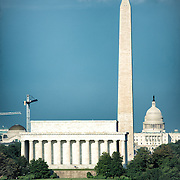 Three of Washington DC's iconic monuments lined up along the National Mall looking towards the east, with the Lincoln Memorial in the foreground, the Washignton Monument in the middle, and the US Capitol Dome in the background. In the bottom of frame is part of the Potomac.