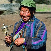 TIBET, Tsangpo Gorge, Tibetan Buddhist villager w/ ritual prayer wheel.