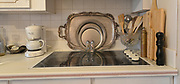 """Silver trays nestled within each other break up the white backsplash behind the kitchen stove. Photo taken on January 8, 2019 for """"At Home"""" feature on Sandy Stolberg, who uses dollar store finds as part of the decorations in her Belleville, IL condo.<br /> Photo by Tim Vizer"""