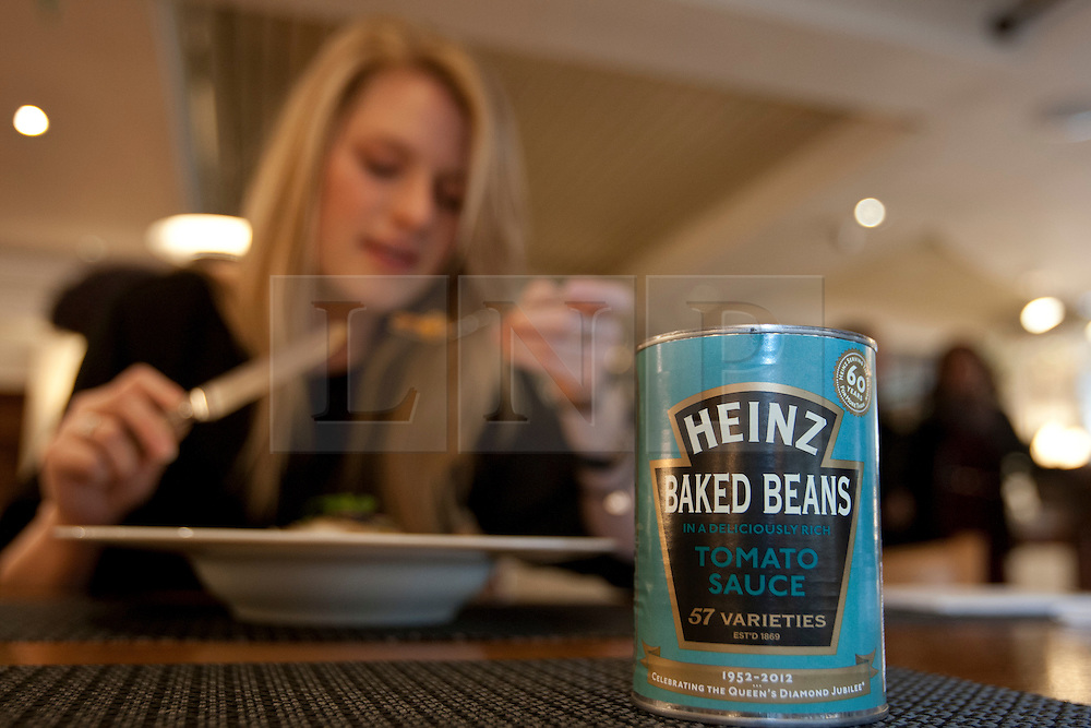 © licensed to London News Pictures. London, UK 23/04/2012. A Fortnum & Mason staff eating a dish made with Heinz beans as Heinz launching a limited edition set of cans to honour the Queens Diamond Jubilee at Fortnum & Mason, this morning (23/04/12). Photo credit: Tolga Akmen/LNP