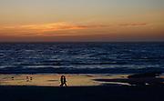 A couple walks on Asilomar State Park, CA, beach at sunset,