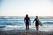 Couple holding their surfboards, walking down the slipway into the breaking waves, ready to go for a surf at St Ouen's Bay, Jersey, CI