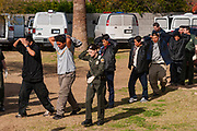 03 MARCH 2003 - PHOENIX, ARIZONA: Immigration and Customs Enforcement officers escort undocumented immigrants discovered in a drop house in Phoenix, AZ, to waiting transport vans. Phoenix police and fire departments responded to reports of a migrant drop house in south central Phoenix and found more than 70 undocumented immigrants in the home. The immigrants were turned over to Immigration and Customs Enforcement (ICE) for processing and eventual removal from the US.      PHOTO BY JACK KURTZ