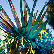 The setting sun hits the top of a colorful head gear kept in blue,greens and golden feathers. The Notting Hill Carnival has been running since 1966 and is every year attended by up to a million people. The carnival is a mix of amazing dance parades and street parties with a distinct Caribbean feel.