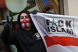 """© Licensed to London News Pictures . 04/01/2014 . London , UK . A demonstration by the English Defence League on Edgware Road against a planned anti-gambling demonstration by """" The Sharia Project """" today (4th January 2014) . An EDL supporter holds a flag with a St George's Cross and the words Fuck Islam . The Sharia Project opposes democracy and wish for a global caliphate governed by Sharia law . Photo credit : Joel Goodman/LNP"""