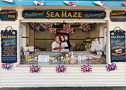 BRIGHTON, UK  29/04/2011. The Royal Wedding of HRH Prince William to Kate Middleton. Across the UK people celebrated the day, even when working. Staff at this traditional fishmongers on Brighton Beach wore masks whilst serving customers. Photo credit should read JULIE EDWARDS/LNP. Please see special instructions. © under license to London News Pictures