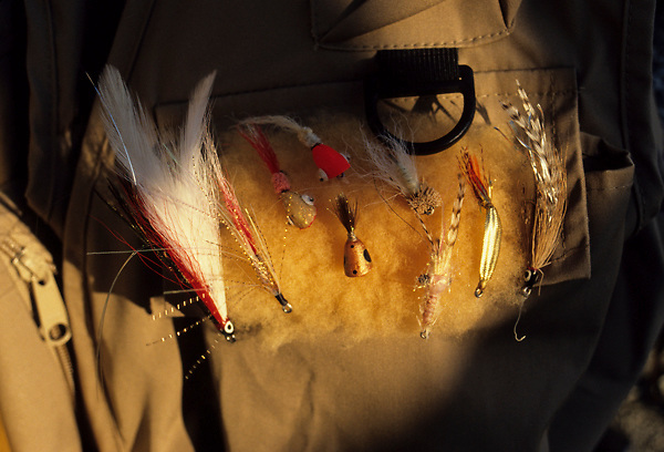 Stock photo of a group of fly fishing lures on a man's fishing vest