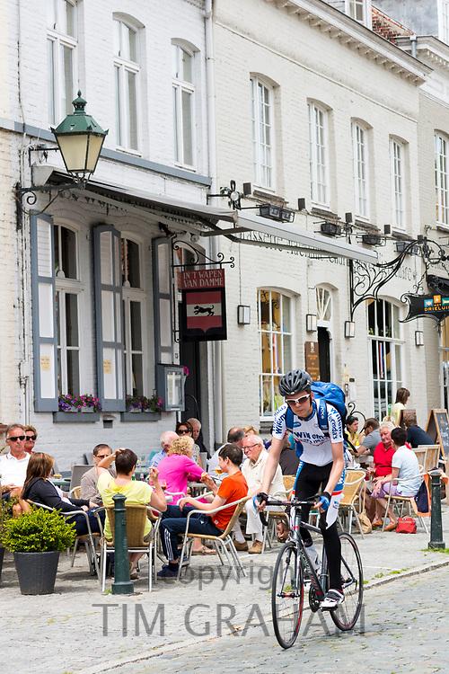 Cyclist cycling past al fresco diners at restaurant in Kerk Straat, Damme, West Flanders, Belgium