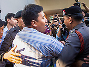 """14 FEBRUARY 2015 - BANGKOK, THAILAND: Thai police lead away Student activist Siriwit Serithiwat after they arrested him during a protest the military coup. Martial law is still in effect in Thailand and protests against the coup are illegal. Dozens of people gathered in front of the Bangkok Art and Culture Centre in Bangkok Saturday to hand out red roses and copies of George Orwell's """"1984."""" Protestors said they didn't support either Red Shirts or Yellow Shirts but wanted a return of democracy in Thailand. The protest was the largest protest since June 2014, against the military government of General Prayuth Chan-Ocha, who staged the coup against the elected government. Police made several arrests Saturday afternoon but the protest was not violent.      PHOTO BY JACK KURTZ"""