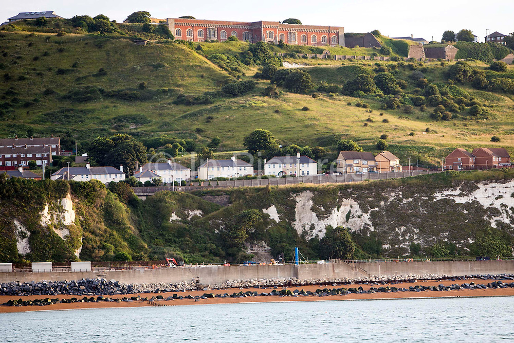 The Western Heights of Dover fortification in the morning sunlight stands at the top of the West Cliffs, with residential buildings of Aycliffe below with Shakespeare beach at the bottom.